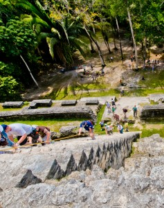 Tourists climbing steps of the High Temple at Lamanai