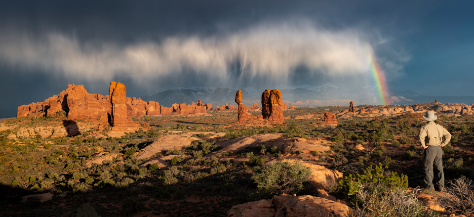 Balanced Rock overlook sunset at Arches National Park with storm and rainbow